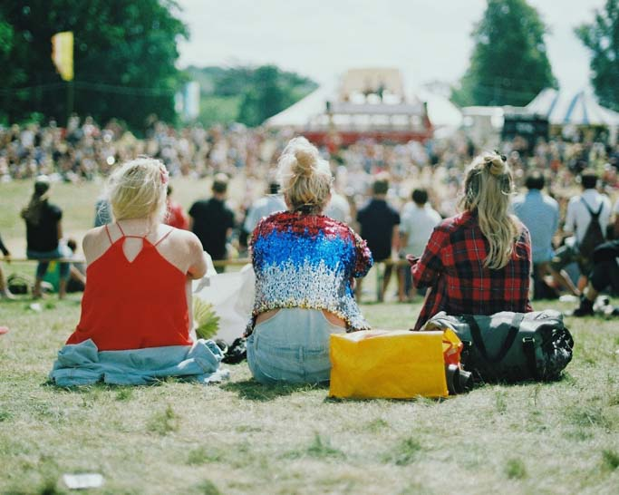Girls sitting in field at concert.