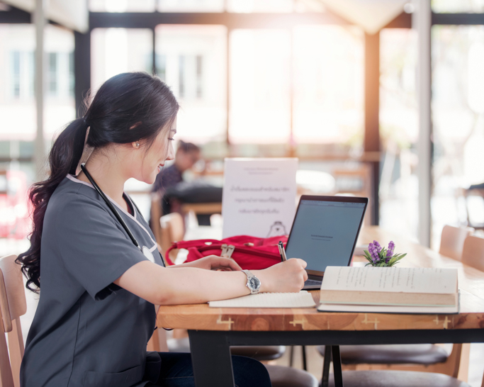 Nurse on laptop in coffee shop.