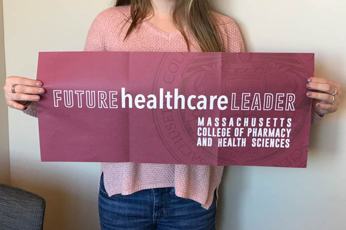 Student holding future healthcare leader sign.