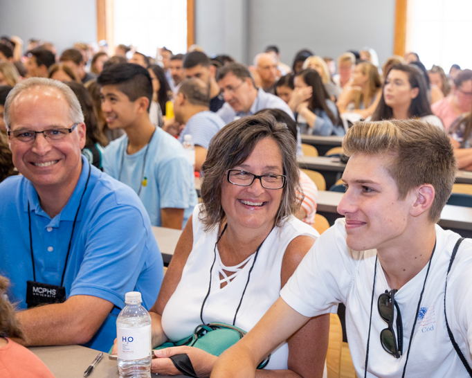 Mom, dad, and son sitting in lecture hall at Orientation.