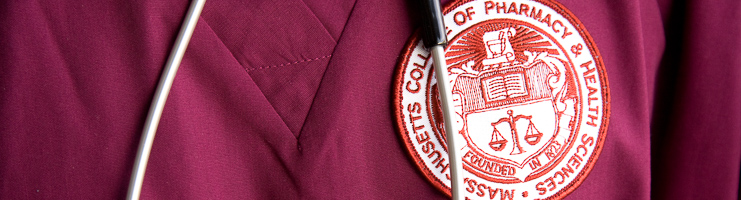 Close-up on student wearing scrubs with MCPHS badge