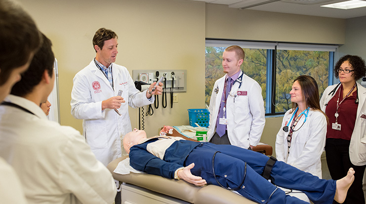 PA students and faculty in class with a simulation dummy.
