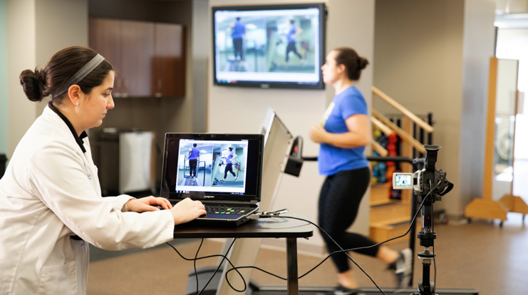 PT student watching patient run on treadmill using a computer assistant.