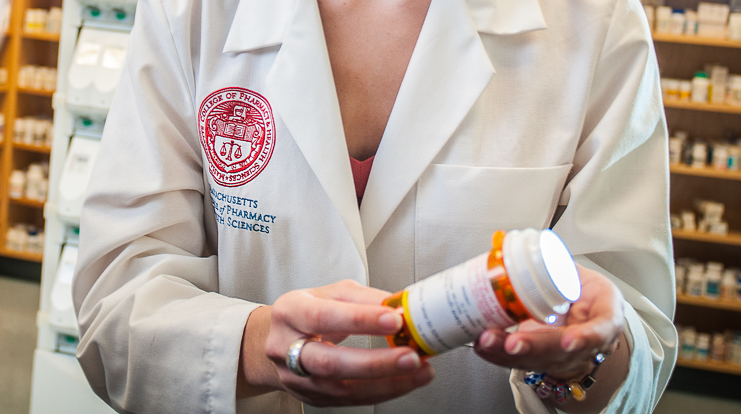 Close up of pharmacy student holding prescription medication.