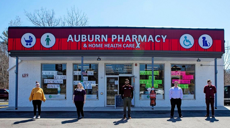 Vrushank Patel with his staff standing outside of his pharmacy in Auburn Massachusetts.