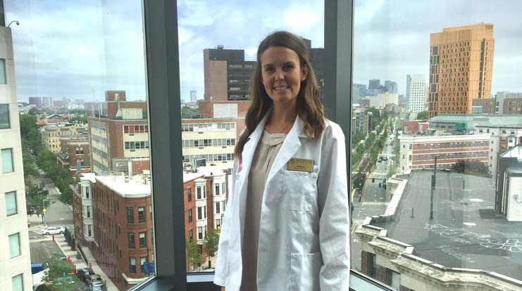 Julia Shriver, a nursing student at MCPHS, standing in front of a window.