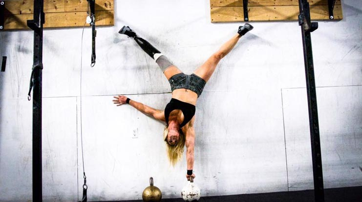 Tina doing handstand against wall on top of kettlebell.