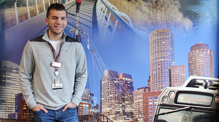 SGA president, Austin Bergeron, standing in front of the new mural in the Student Lounge.