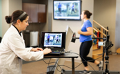 Physical therapy student watching patient on treadmill using computer assistance.